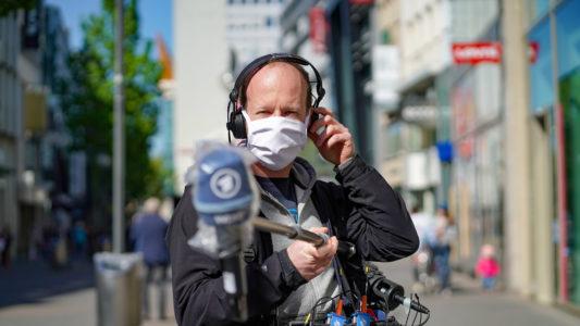 Ein Radioreporter hält das Mikrofon mit einer Tonangel weit von sich weg